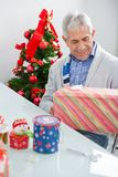Man Looking At Wrapped Christmas Present Stock Photos