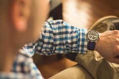 Man looking at wrist watch. Casually dressed man looking at wrist watch Stock Image