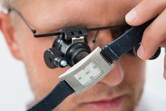 Man Looking Wrist Watch With Loupe Stock Images