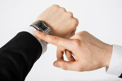 Man looking at wristwatch. Close up of man looking at wristwatch Royalty Free Stock Images
