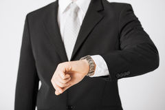 Man looking at wristwatch Stock Images