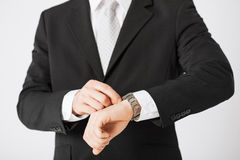 Man looking at wristwatch. Close up of man looking at wristwatch Royalty Free Stock Photo