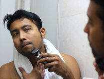 Man lookingIndian asian after his appearance in front of a mirror beauty styling lifestyle. Shaving routine. S Royalty Free Stock Photo