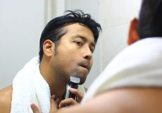 Man lookingIndian asian after his appearance in front of a mirror beauty styling lifestyle. Shaving routine. S Stock Images