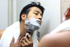 Man lookingIndian asian after his appearance in front of a mirror beauty styling lifestyle. Shaving routine. S Royalty Free Stock Photography