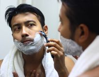 Man lookingIndian asian after his appearance in front of a mirror beauty styling lifestyle. Shaving routine. S Stock Photo