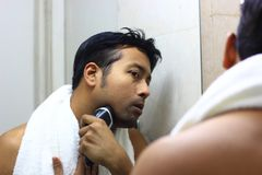 Man looking after his appearance in front of a mirror beauty styling lifestyleman lookingIndian asian after his appearance in fron. Man lookingIndian asian after Stock Photos
