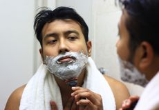 Man lookingIndian asian after his appearance in front of a mirror beauty styling lifestyle. Shaving routine. S Stock Photography