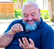Man looks amused the news on the smartphone. Adult man, bald, bearded  and overweight looks amused at the good news on the smartphone Stock Photo