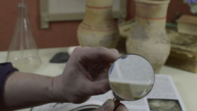 A man looks at an antique arrowhead. A man looks at an antique tip for an arrow through a magnifying glass stock video footage