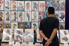 Man Looks at Artwork at Comicon Royalty Free Stock Photos