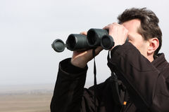 Man looks through binoculars Royalty Free Stock Image