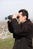 Man looks through binoculars Royalty Free Stock Images