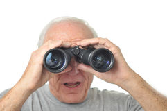 Man looks through binoculars into the distance Royalty Free Stock Photography