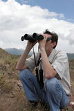 Man looks through binoculars in mountains Royalty Free Stock Photography