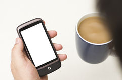 Man looks at blank smartphone. A stock photo of a man drinking coffee and looking at a blank smartphone Royalty Free Stock Image