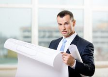 Man looks at blueprint in hands. Man wearing suit and blue tie looks at blueprint in hands Stock Photography