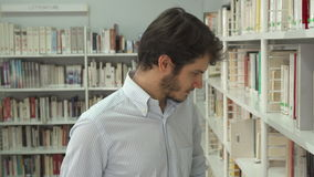 Man looks for a book at the library. Young brunette man looking for a book at the library. Attractive bearded guy coming closer to the book rack. Close up of stock footage
