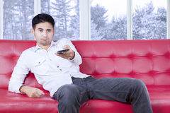 Man looks bored watching tv at home Royalty Free Stock Photography