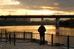 Man looks on the bridge. During sunset Royalty Free Stock Images
