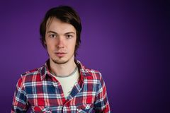 The man looks at the camera sternly. Portrait of a serious man in a plaid shirt on a purple background, copy space.  Royalty Free Stock Photo