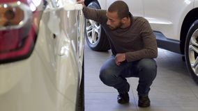 Man looks at the car wheel at the dealership. Handsome african american man looking at the car wheel at the showroom. Young bearded guy squating near the white Royalty Free Stock Images