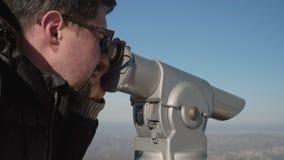 Man looks at city through observation binoculars. Man tourist looks at cityscape under blue sky through binoculars on observation deck close view stock footage