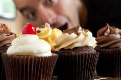 Man Looks At Cupcakes Royalty Free Stock Photos