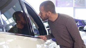 Man looks at different cars at the dealership. Attractive black man looking at different cars at the showroom. Handsome african american guy choosing vehicle at Stock Photo