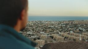 Man looks forward to the horizon during sunset, blue sea and clear sky in Dahab, Egypt, 4k