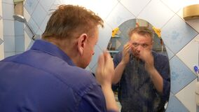 A man looks at himself in the mirror