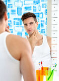 Man looks at himself in mirror Stock Photo