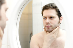 Man looks at his beard Royalty Free Stock Images