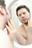Man looks at his beard. And thought about shaving royalty free stock photography