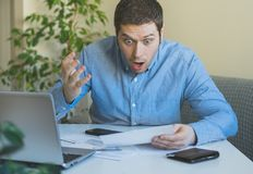Man looks at his bills. Handsome man indignantly looks at his monthly bills Stock Image