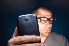 Man looks at his smartphone Stock Photo