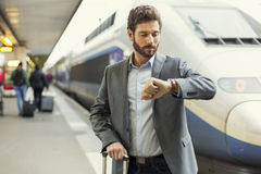 Man looks his watch on the platform station Stock Photos