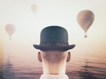 Man looks at hot air balloons. Man wearing a hat and looking at hot air balloons flying through the sky. This is a 3d render illustration Stock Photography