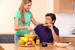 Man looks how his young wife pours orange juice Royalty Free Stock Photos