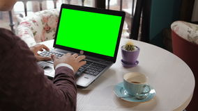 Man looks at the laptop screen. Caucasian man looking at the laptop screen with green background. Brunette guy using touchpad of laptop with chroma key on it's stock footage