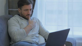 Man looks at the laptop screen at home. Attractive brunette man looking at the laptop screen at home. Middle aged bearded man touching his chin by his hand while stock footage