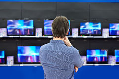 Man looks at LCD TVs in store Royalty Free Stock Image