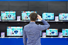 Man looks at LCD TVs in store Royalty Free Stock Images