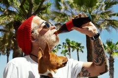 Man, looks like a santa, drinks a soda lemonade his dog looks at him Royalty Free Stock Photo