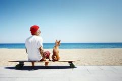 Man, looks like a santa, ride longboard on the beach Royalty Free Stock Photos