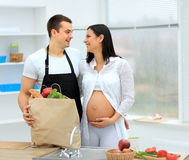 Man looks lovingly at his pregnant. Wife in the background of the kitchen Stock Photo
