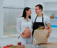 Man looks lovingly at his pregnant wife in the background of the kitchen. stock photography