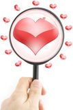 The man looks in a magnifier at heart Stock Photography