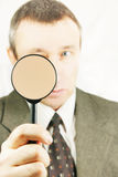 Man looks through a magnifying glass. Isolated over white background Royalty Free Stock Photography