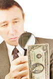 Man looks through a magnifying glass on the dollar banknote Stock Photography